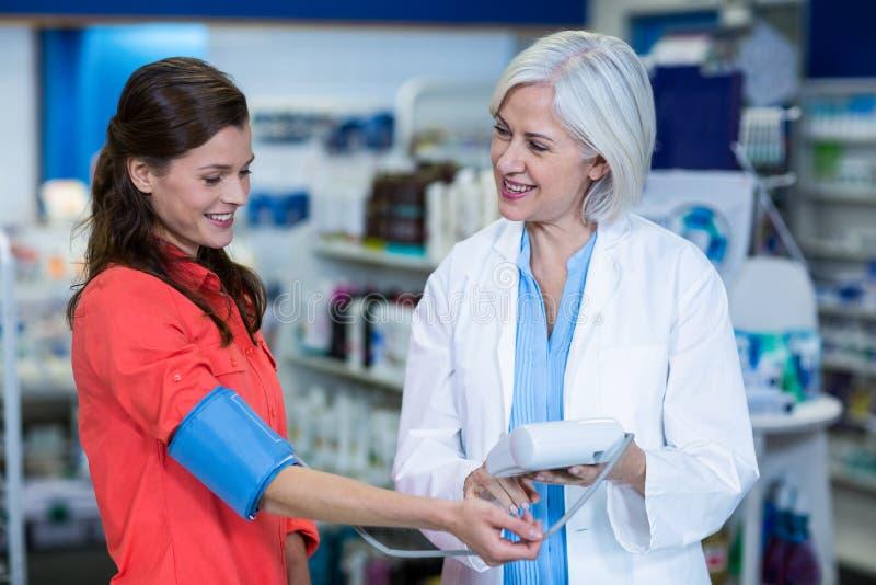 Farmacéutico que comprueba la presión arterial del cliente fotografía de archivo