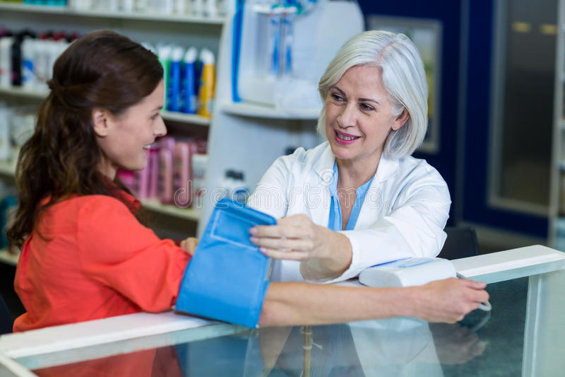Farmacéutico que comprueba la presión arterial del cliente imagen de archivo libre de regalías