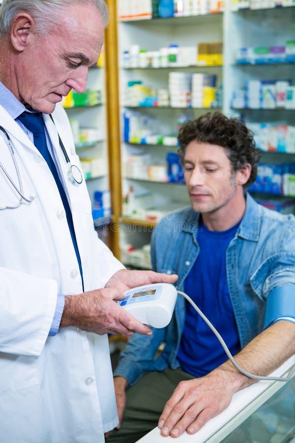 Farmacéutico que comprueba la presión arterial del cliente foto de archivo