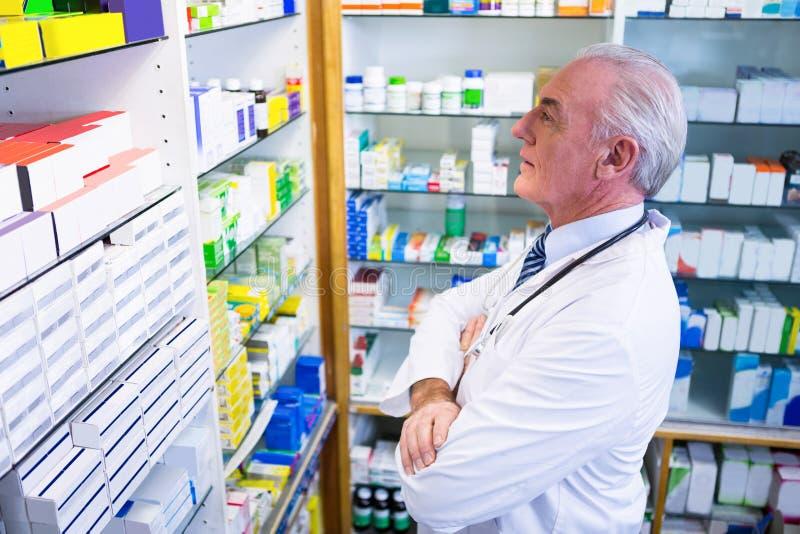 Farmacéutico que comprueba medicinas en farmacia foto de archivo