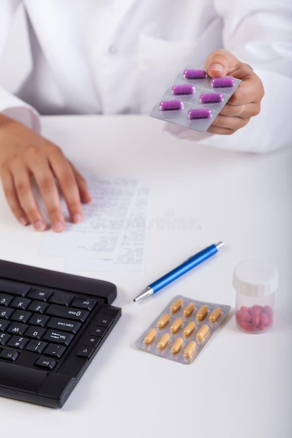 Farmacéutico que da cápsulas violetas pacientes fotografía de archivo libre de regalías