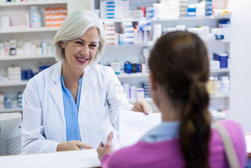 Farmacéutico que da prescripciones de la medicina al cliente imagenes de archivo