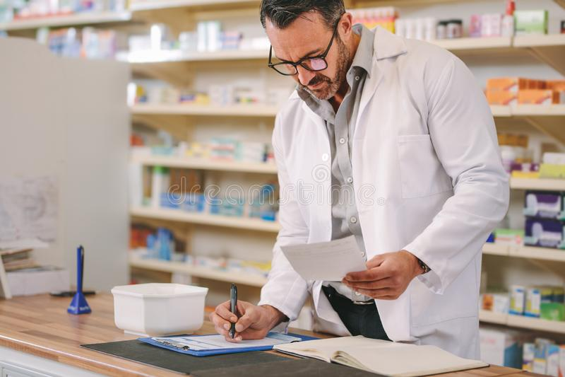 Farmacéutico que escribe el contador de la farmacia de la prescripción imágenes de archivo libres de regalías