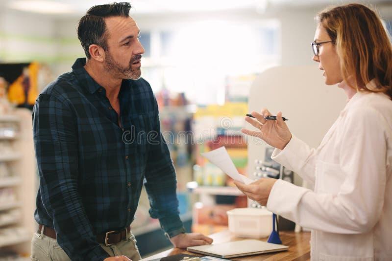 Farmacéutico que explica una prescripción al cliente imagen de archivo
