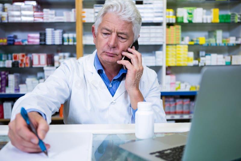 Farmacéutico que habla en el teléfono móvil mientras que escribe prescripciones fotografía de archivo