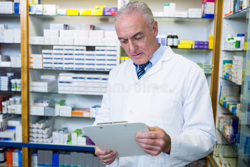 Farmacéutico que lee una prescripción fotos de archivo