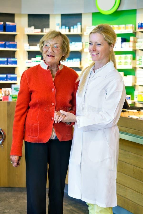 Farmacéutico que lleva a cabo la mano del cliente imagen de archivo libre de regalías