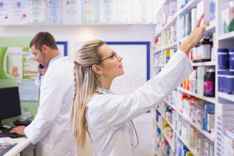 Farmacéutico que mira para arriba las medicinas foto de archivo libre de regalías