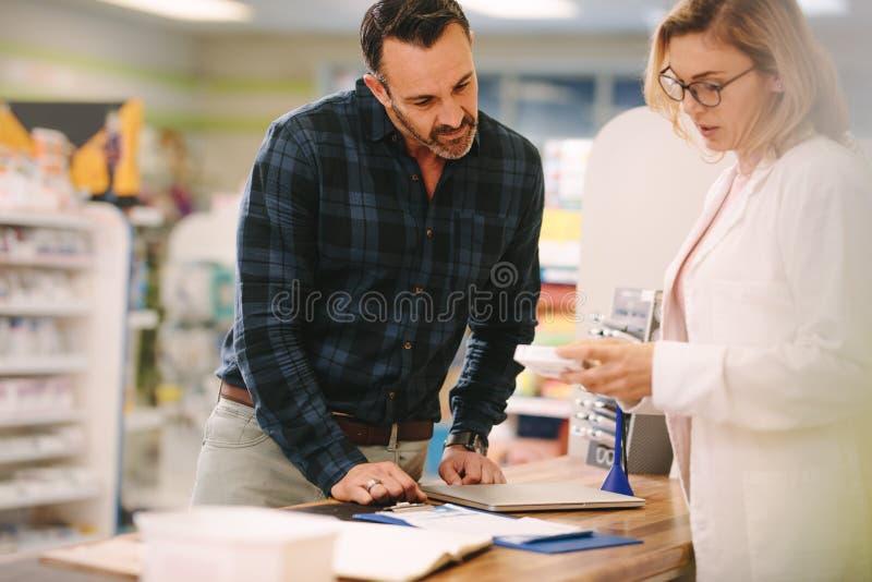 Farmacéutico que muestra la medicina al cliente en farmacia imagen de archivo