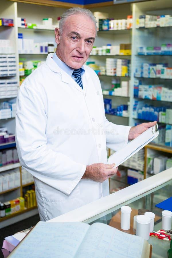 Farmacéutico que sostiene un tablero en farmacia fotos de archivo