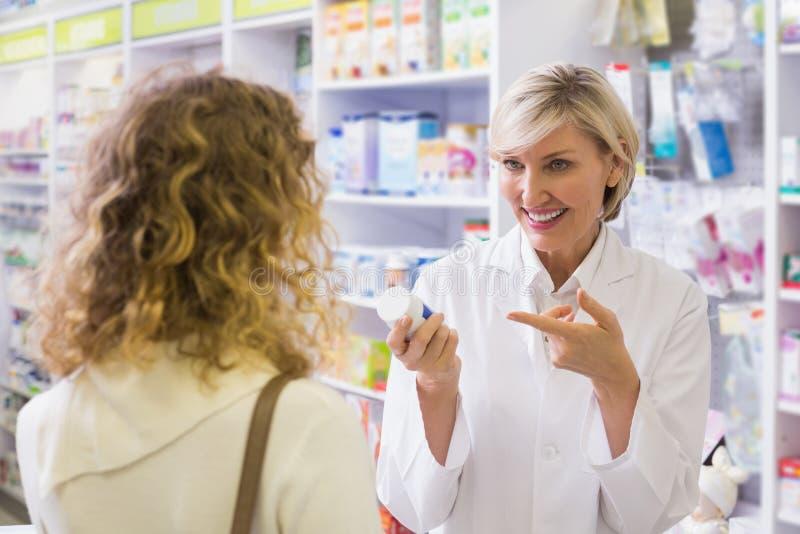 Farmacéutico que sostiene una botella de drogas que hablan con el cliente fotos de archivo