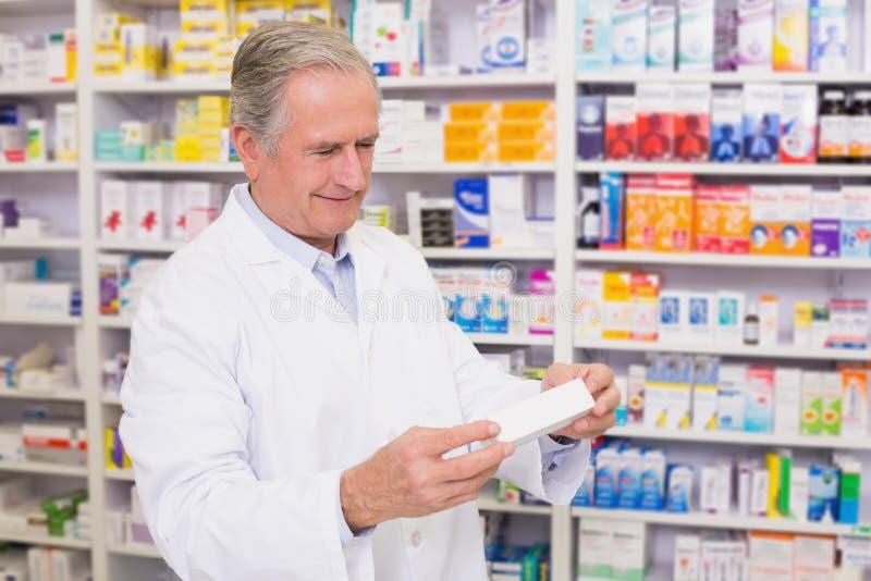 Farmacéutico que sostiene una caja de píldoras mientras que lee la etiqueta foto de archivo
