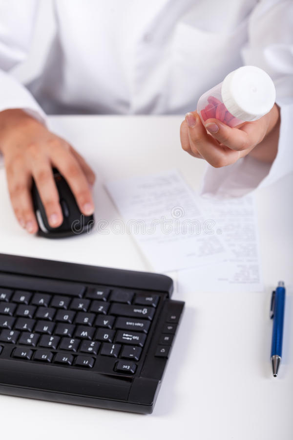 Farmacéutico que usa el ordenador durante trabajo imagenes de archivo