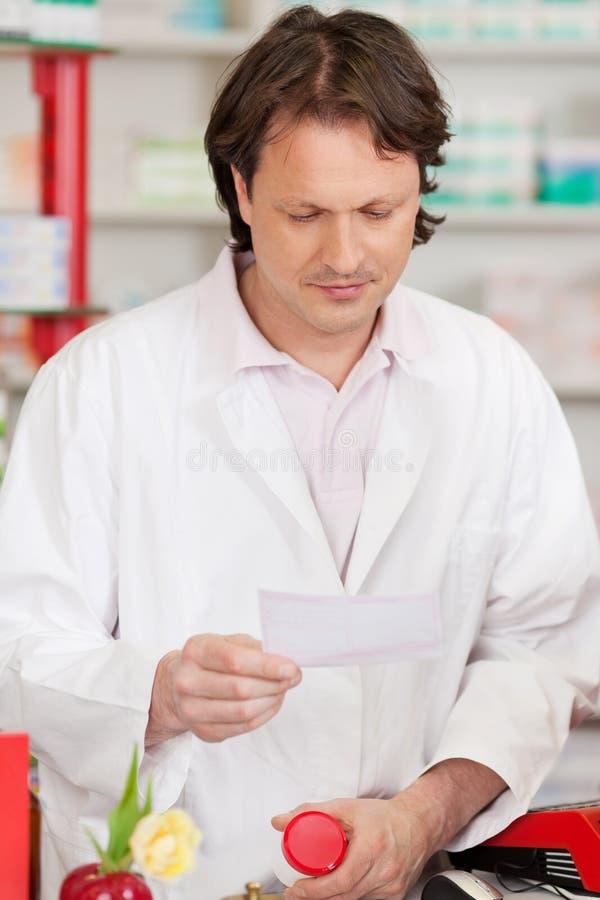 Farmacéutico Reading Prescription Paper mientras que sostiene Bot de la medicina imagen de archivo