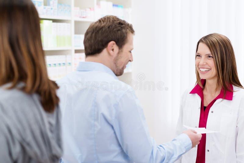 Farmacéutico sonriente amistoso que ayuda a un cliente foto de archivo
