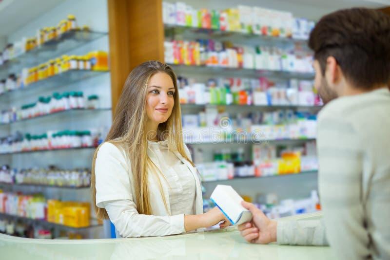 Farmacéutico sonriente atractivo que le da píldoras del cliente fotos de archivo libres de regalías