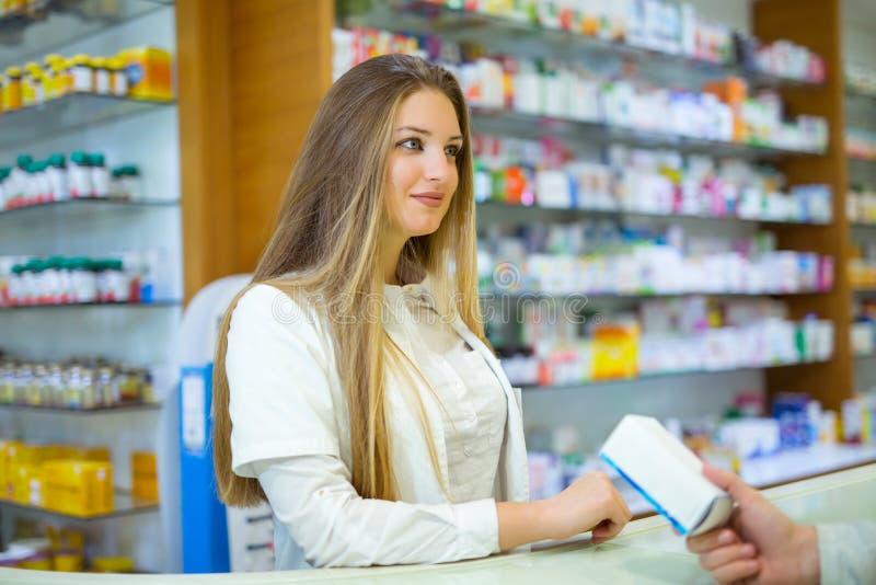 Farmacéutico sonriente atractivo que le da píldoras del cliente foto de archivo libre de regalías
