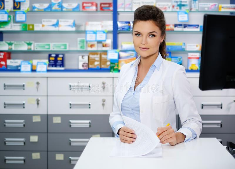 Farmacéutico sonriente hermoso de la mujer joven que hace el suyo trabajo en farmacia fotografía de archivo libre de regalías