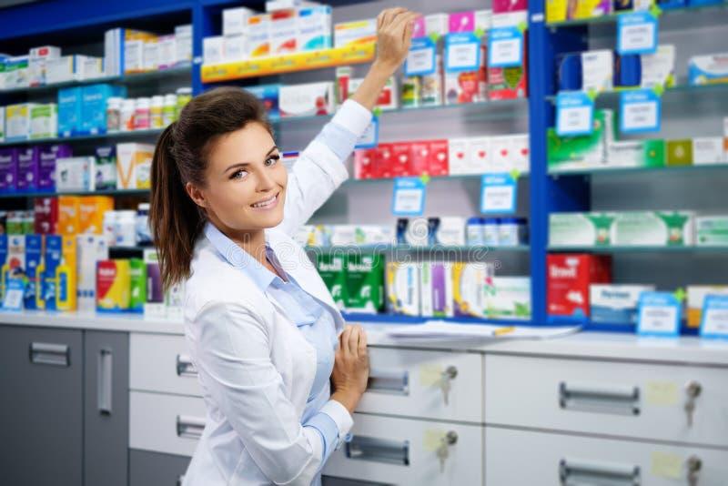 Farmacéutico sonriente hermoso de la mujer joven que hace el suyo trabajo en farmacia foto de archivo libre de regalías