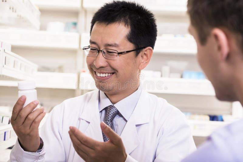 Farmacéutico sonriente que muestra la medicación de la prescripción a un cliente imagen de archivo libre de regalías