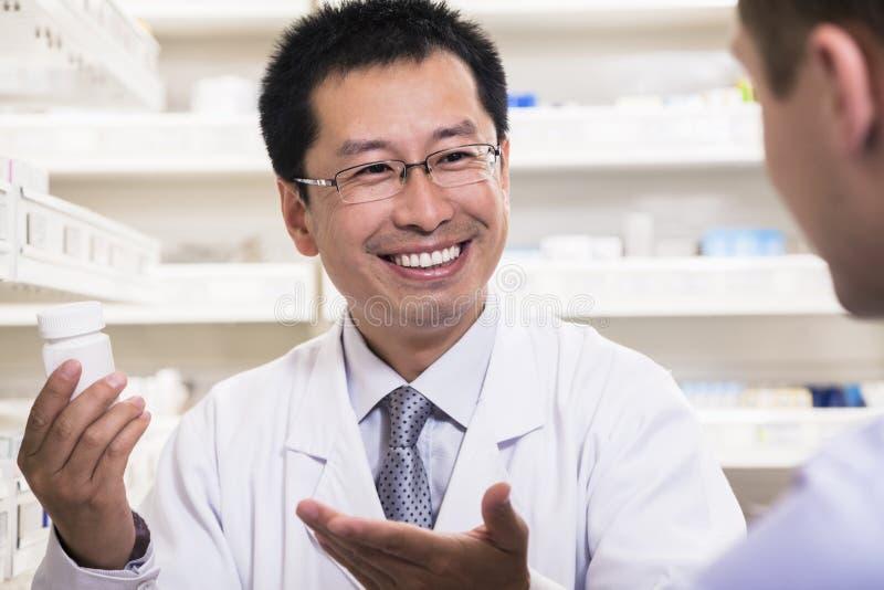 Farmacéutico sonriente que muestra la medicación de la prescripción a un cliente imágenes de archivo libres de regalías