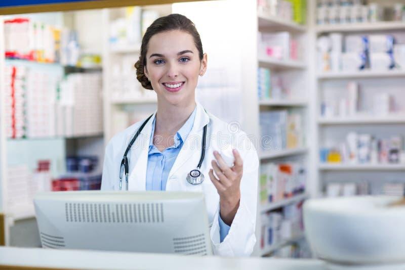 Farmacéutico sonriente que sostiene el envase de la medicina en farmacia foto de archivo