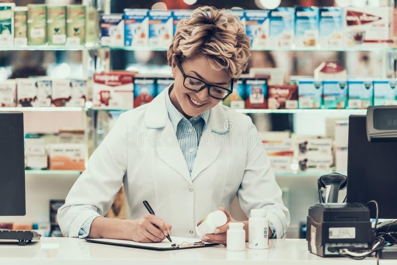 Farmacéutico sonriente Working del retrato en droguería foto de archivo