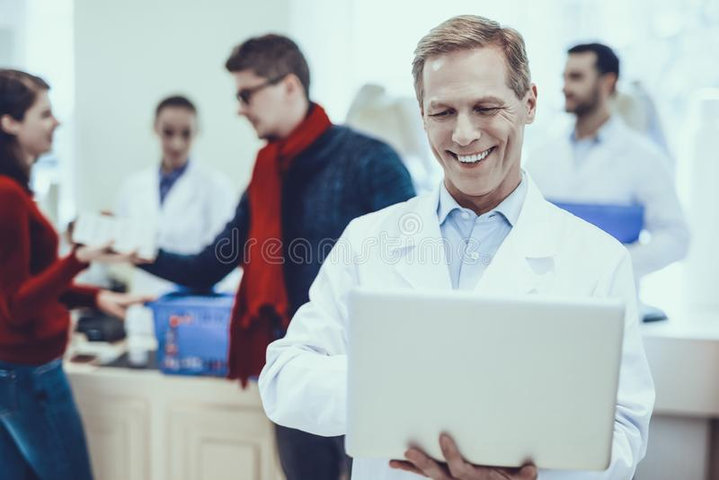 Farmacéutico Using un ordenador portátil en farmacia foto de archivo