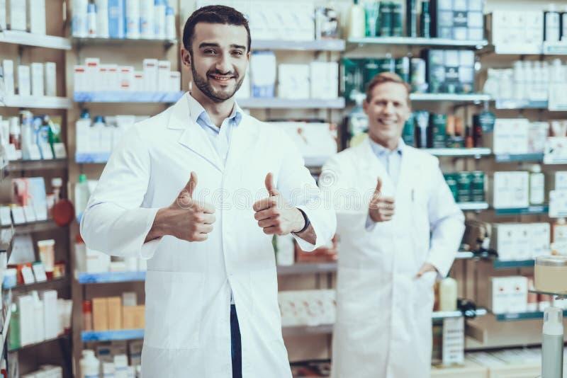 Farmacéuticos de sexo masculino que presentan en farmacia foto de archivo libre de regalías