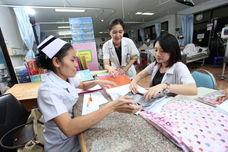 Farmacéuticos que comprueban la información de los pacientes con la enfermera de la sala imagen de archivo