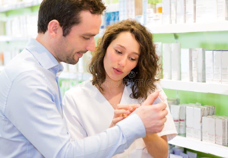 Farmacêutico atrativo que recomenda um cliente fotografia de stock