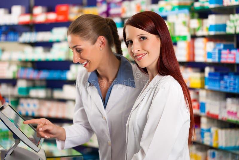 Farmacêutico com o assistente na farmácia foto de stock