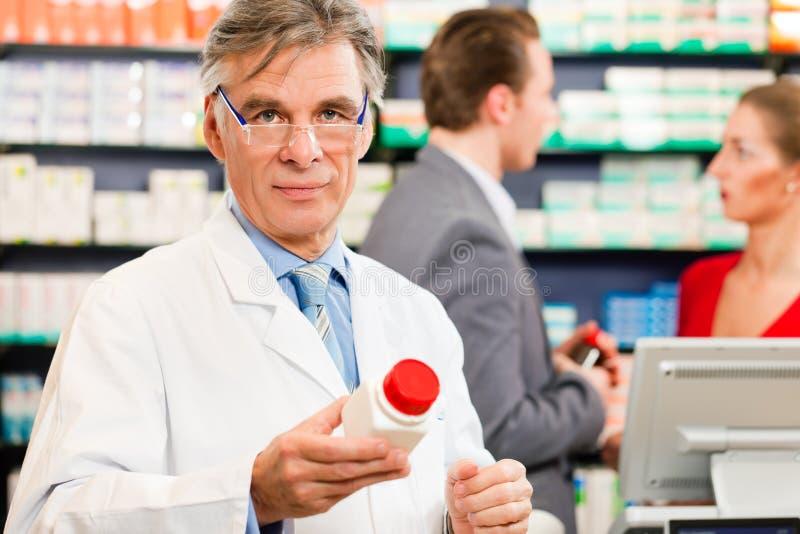 Farmacêutico com os clientes na farmácia fotografia de stock