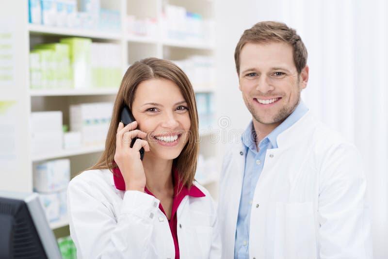 Farmacêutico de sorriso que conversa no telefone imagem de stock royalty free