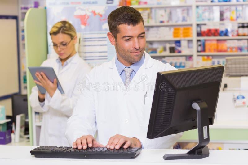 Farmacêutico de sorriso que usa o computador fotografia de stock