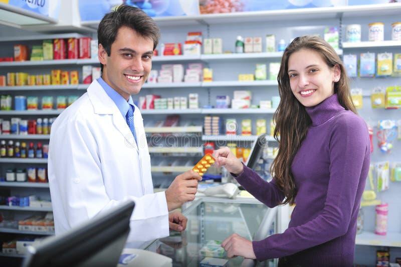 Farmacêutico e cliente na farmácia fotos de stock royalty free