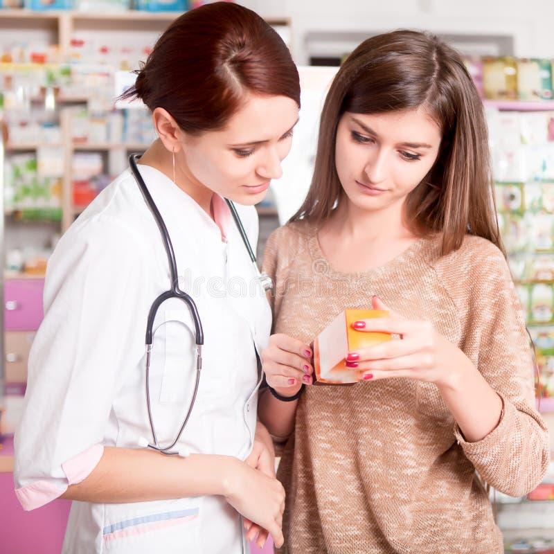 Farmacêutico e cliente que olham a caixa da medicamentação fotos de stock