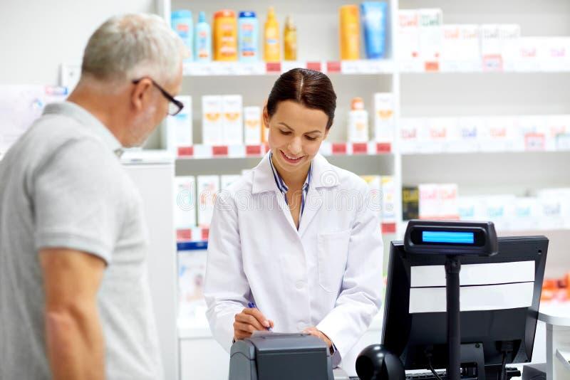 Farmacêutico e cliente superior na farmácia fotos de stock