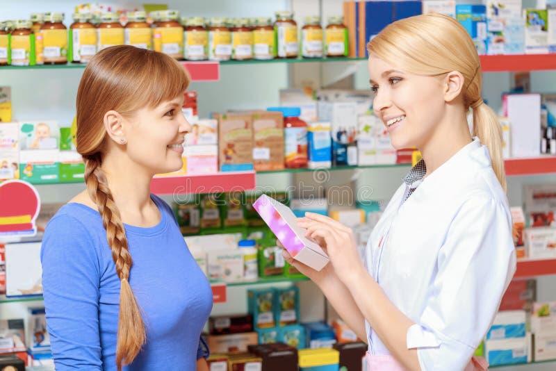 Farmacêutico e um cliente que escolhe a medicina foto de stock royalty free
