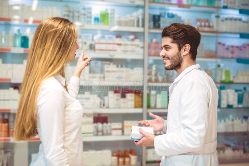 Farmacêutico experiente que aconselha o cliente fêmea na farmácia foto de stock royalty free