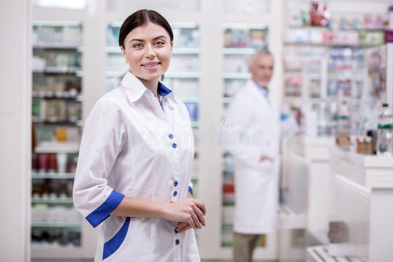 Farmacêutico fêmea alegre que espera clientes foto de stock royalty free