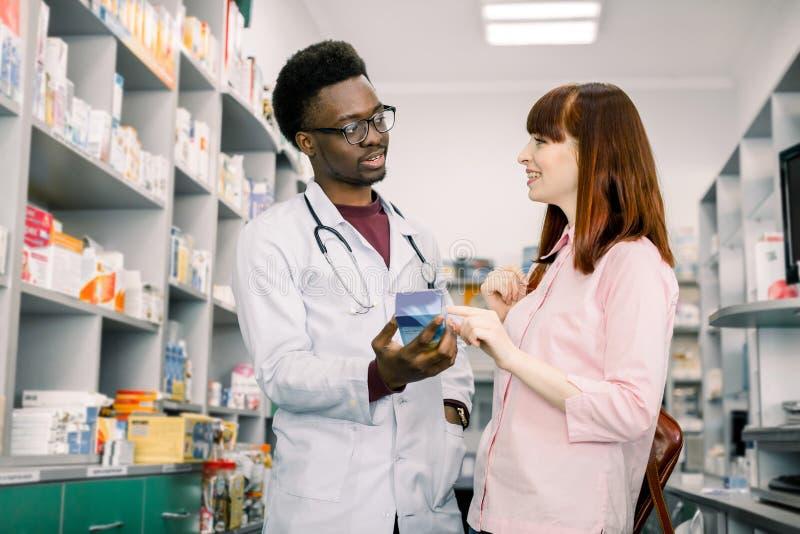 Farmacêutico masculino africano considerável que fala com um cliente fêmea bonito na farmácia clara moderna imagem de stock royalty free