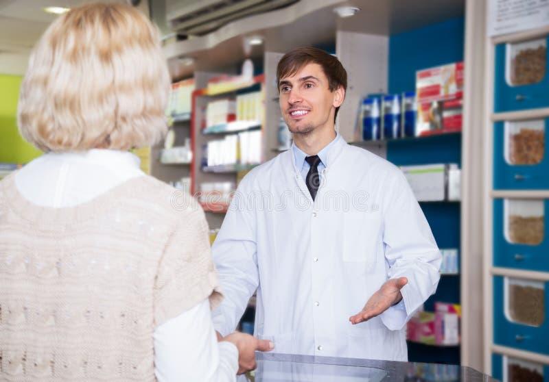 Farmacêutico masculino que fala ao cliente na farmácia imagens de stock