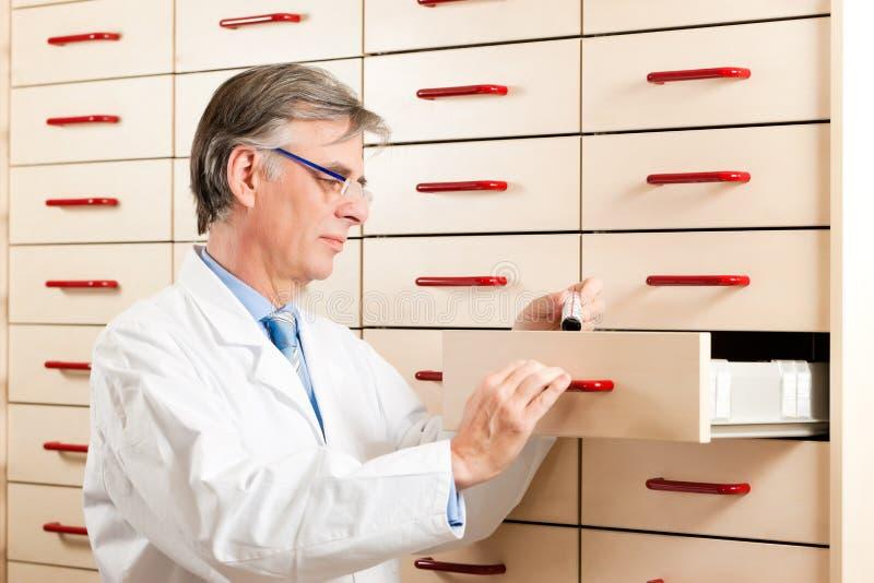 Farmacêutico na frente da caixa de medicina foto de stock royalty free