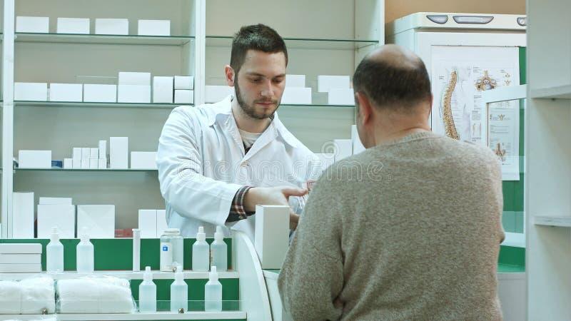 Farmacêutico novo que dá a droga ao cliente do homem superior e que toma o pagamento nos dólares na drograria imagem de stock royalty free