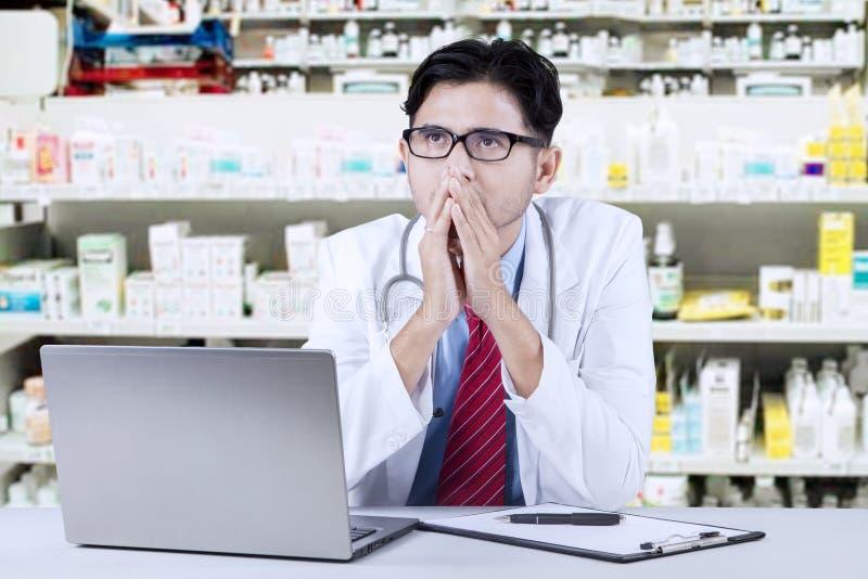 Farmacêutico pensativo que senta-se na drograria imagens de stock