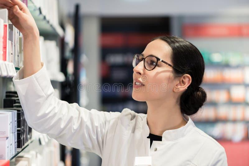 Farmacêutico que está na frente dos vários produtos que pensam ao valor máximo de concentração no trabalho imagens de stock