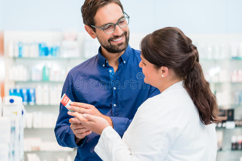 Farmacêutico que fala ao cliente na farmácia fotos de stock royalty free