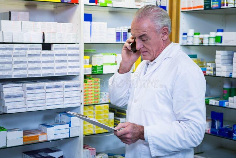 Farmacêutico que fala no telefone celular ao verificar medicinas foto de stock royalty free