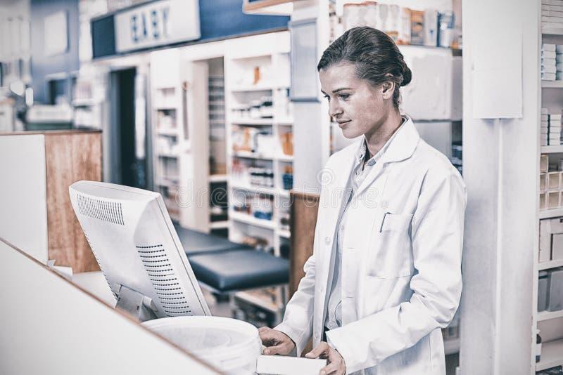 Farmacêutico que faz um registro prescrição através do computador fotografia de stock royalty free